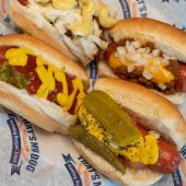 The idea of placing a sausage on a split roll probably dates to the 1890s. The condiments came later, even after Upton Sinclair did his best to quell the trend.